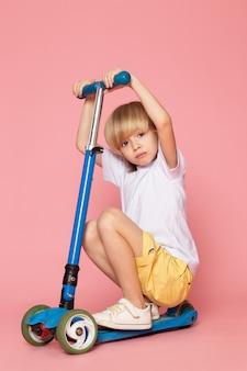 Niño pequeño en camiseta blanca montando scooter en pared rosa