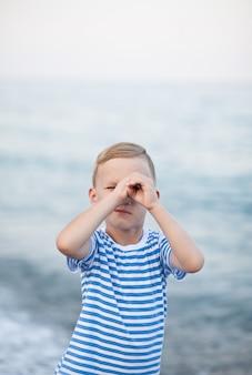 Niño pequeño en camiseta a rayas jugando en la playa con fondo borroso junto al mar