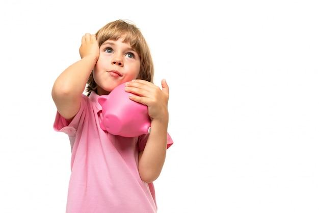 Niño pequeño en una camiseta rosa con una alcancía sobre un fondo blanco.