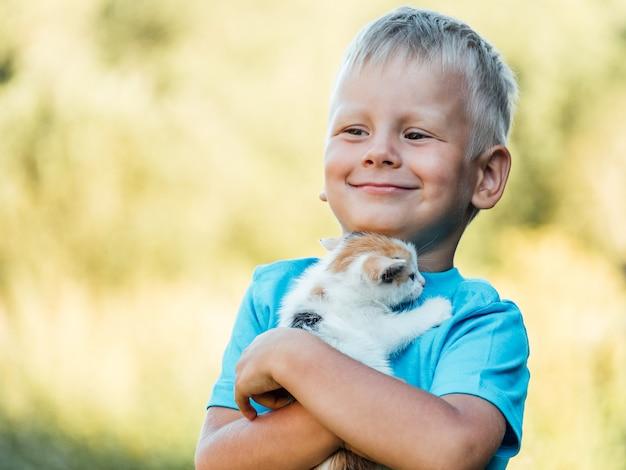 Niño pequeño en el campo con su adorable gatito esponjoso