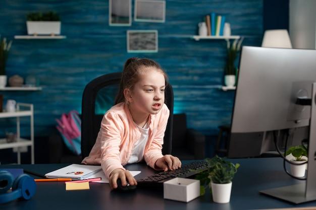Niño pequeño cansado con exceso de trabajo navegando por la información de la escuela en la computadora