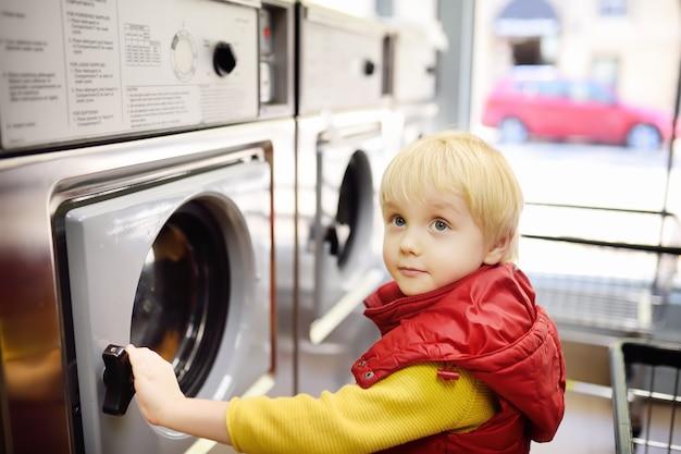 Un niño pequeño carga ropa en la lavadora en lavandería pública.