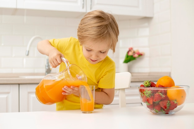 Niño pequeño en casa vertiendo jugo