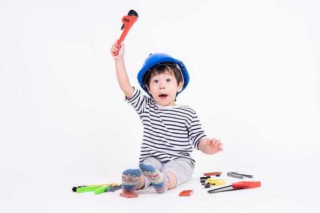 Niño pequeño con casco azul sentado y jugando con juguetes de equipos de construcción en blanco