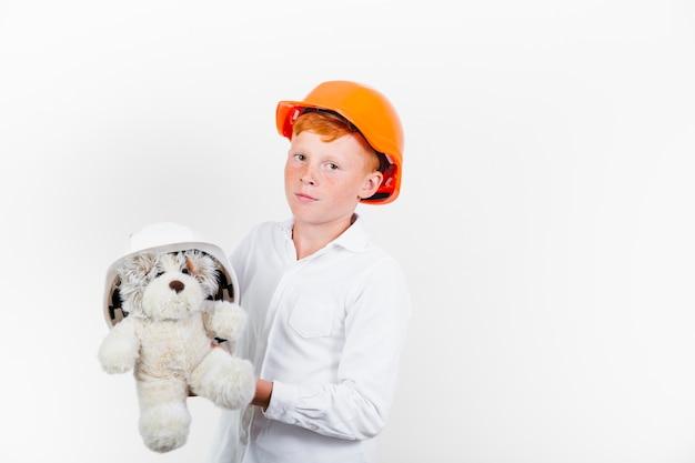 Niño pequeño con casco de seguridad y osito de peluche