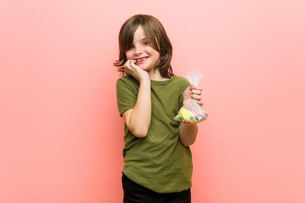 Niño pequeño caucásico con caramelos mordiendo las uñas, nervioso y muy ansioso.