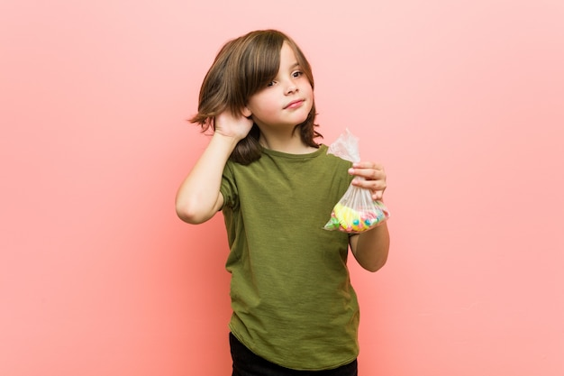 Niño pequeño caucásico con dulces tratando de escuchar un chisme