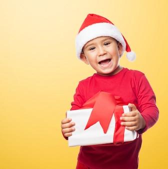 Niño pequeño celebrando la navidad con un regalo