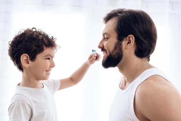 El niño pequeño está cepillando los dientes del hombre barbudo con el cepillo de dientes.