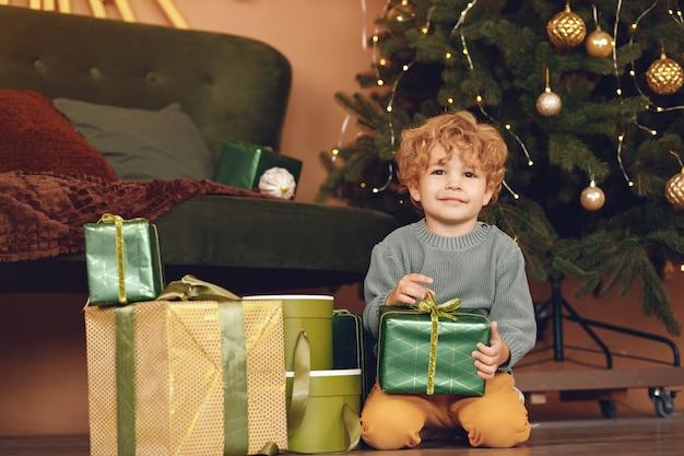 Niño pequeño cerca del árbol de navidad en un suéter gris