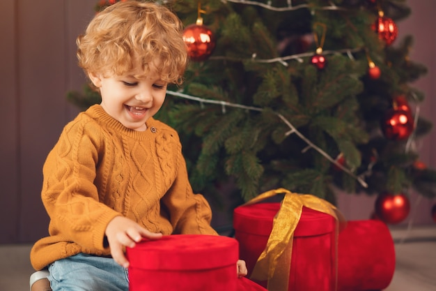 Niño pequeño cerca del árbol de navidad en un suéter marrón
