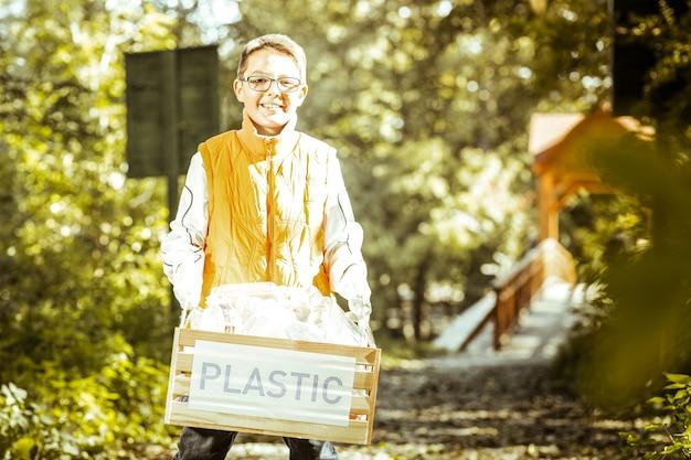 Un niño pequeño en chaleco naranja posando en la pista forestal con una caja de plástico en un buen día