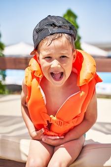Niño pequeño en un chaleco salvavidas se sienta y se ríe en la playa