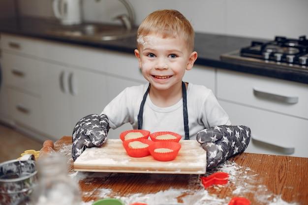 Niño pequeño cocinar la masa para galletas
