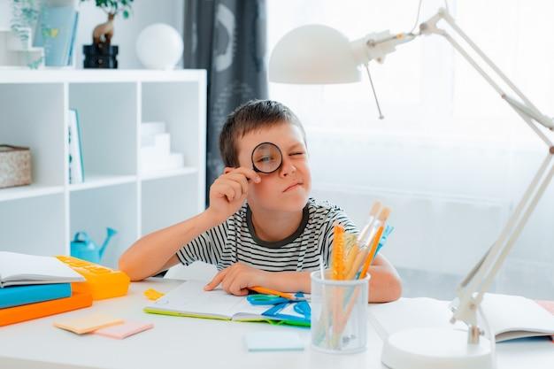 El niño pequeño colegial está sentado en casa en la mesa y resuelve la tarea mirando a través de una lupa. regreso a la escuela, preparación, educación en casa.