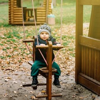 Niño pequeño en columpio en jardín de otoño