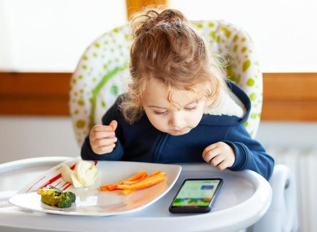 El niño pequeño come mientras ve películas en el teléfono móvil.