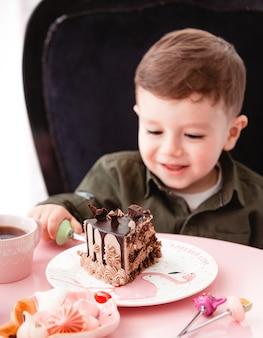 Niño pequeño come pastel de chocolate