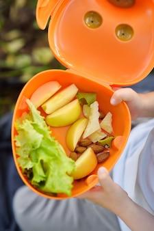 El niño pequeño está comiendo su almuerzo en la hierba en parque en verano.