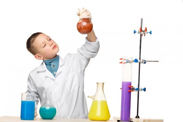 Niño pequeño como químico haciendo experimento con fluido químico en el laboratorio