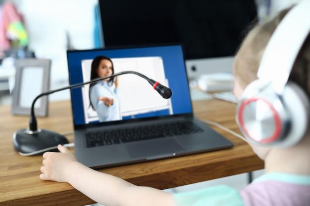 El niño pequeño se comunica en línea con el maestro