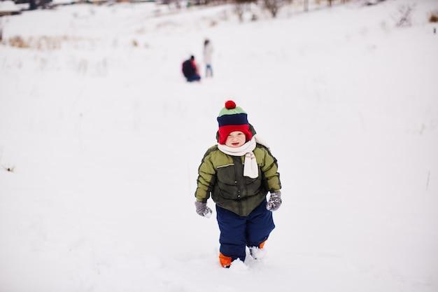 Niño pequeño está corriendo en algún lugar en la nieve