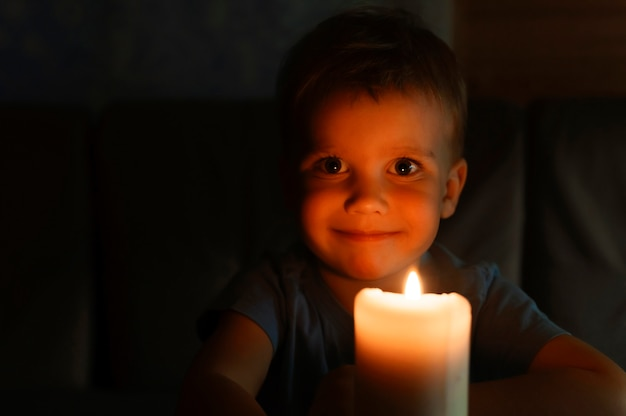 Niño pequeño de cuatro años admira una vela de cera encendida en la noche en casa