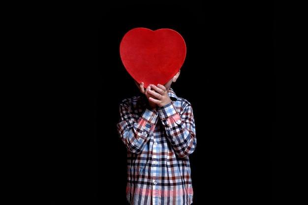 El niño pequeño cubre la cara con el cuadro rojo en forma de corazón en la oscuridad