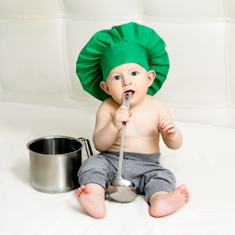 Niño pequeño con cucharón de metal y gorro de cocinero