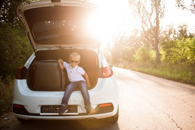 Niño pequeño descansando al costado de la carretera en un viaje por carretera
