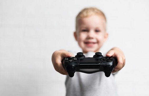 Niño pequeño desenfocado que sostiene un controlador