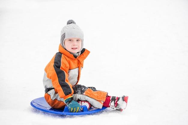 Niño pequeño se desliza cuesta abajo en el plato de nieve