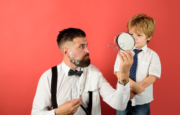 El niño pequeño del día del padre sostiene el espejo para el padre barbero afeitado barbudo en el cuidado de la barba de la barbería