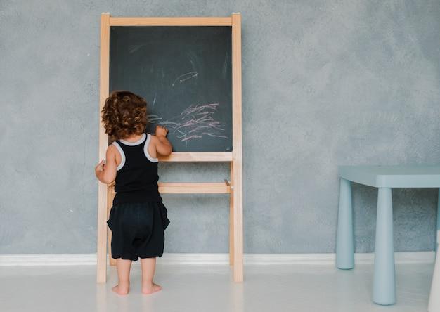 Niño pequeño dibuja con tiza sobre una pizarra negra tablero en casa en la guardería contra una pared gris.