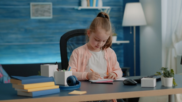 Niño pequeño dibujo con lápices de colores en el cuaderno en el escritorio