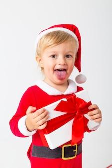 Un niño pequeño con un disfraz de santa se encuentra sobre un fondo blanco junto a cajas de regalo para navidad. concepto de navidad, espacio de texto