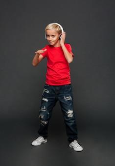Niño pequeño emocional escuchar música con auriculares bailando.
