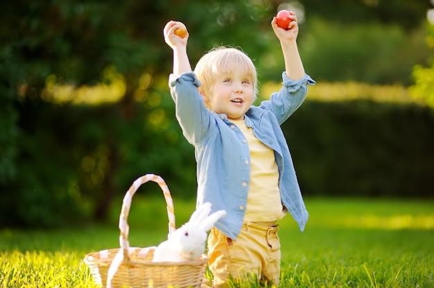 Niño pequeño encantador que caza huevos de pascua en el parque de la primavera el día de pascua