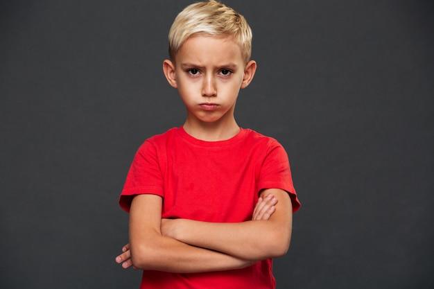 Niño pequeño enojado con los brazos cruzados.