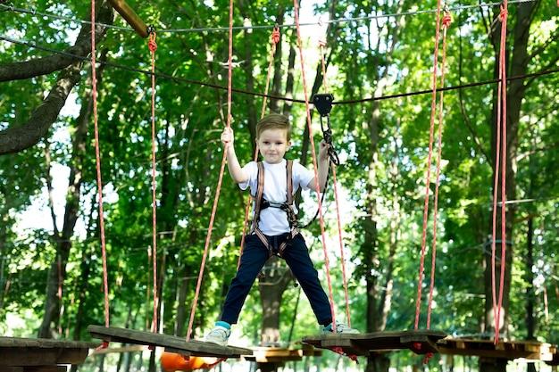Un niño pequeño con equipo de escalada está caminando por un camino de cuerdas en un parque de aventuras, agarrado a una cuerda y un mosquetón.