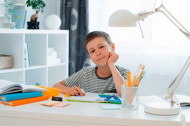 El niño pequeño escolar está sentado en la mesa en casa y está resolviendo la tarea. regreso a la escuela, preparación, educación en casa.