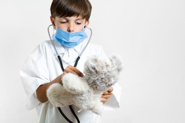 Niño pequeño con estetoscopio y oso de peluche