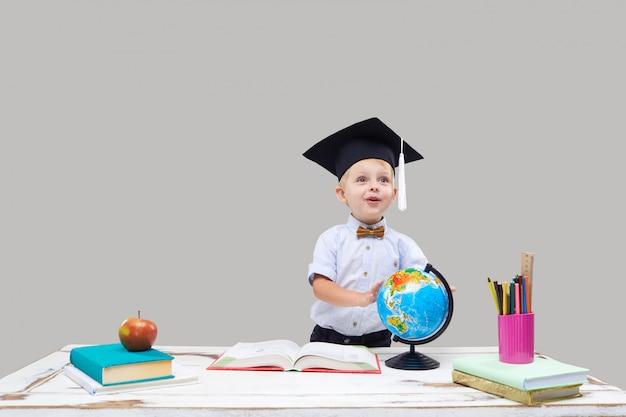 El niño pequeño está estudiando mientras usa un gorro de graduación en una pared aislada gris