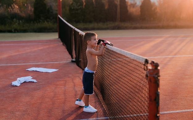 Niño pequeño feliz lindo que se coloca en el patio del tenis que se inclina en red del tenis.