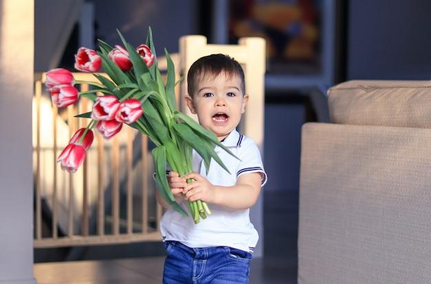 Niño pequeño feliz lindo que sostiene el ramo de tulipanes rojos. las madres o el día de san valentín.