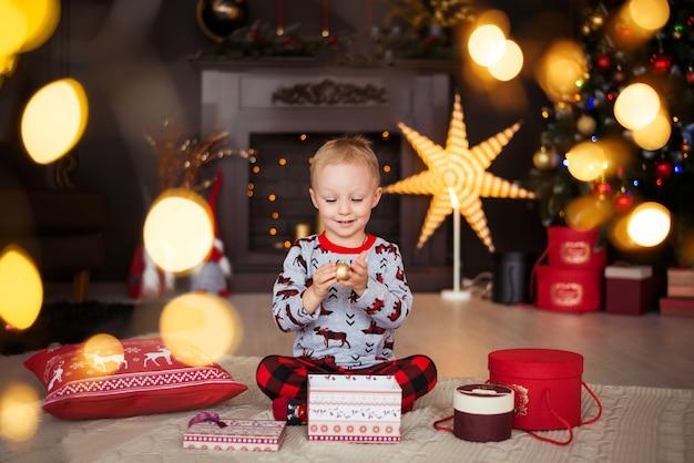 Niño pequeño feliz que se sienta en el fondo de la chimenea y del árbol de navidad con los regalos.