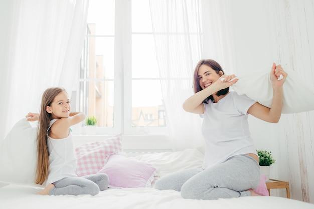 El niño pequeño feliz sostiene la almohada, se pelea junto con su madre, se divierte en el dormitorio, disfruta del tiempo libre