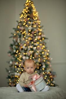 Niño pequeño en el fondo del árbol de navidad