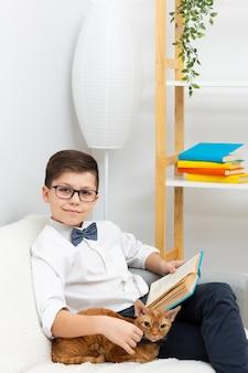 Niño pequeño con gato leyendo