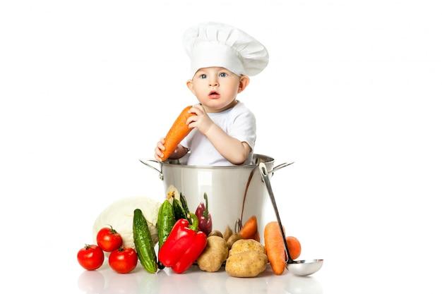 Niño pequeño en gorro de cocinero con cucharón, pan y verduras